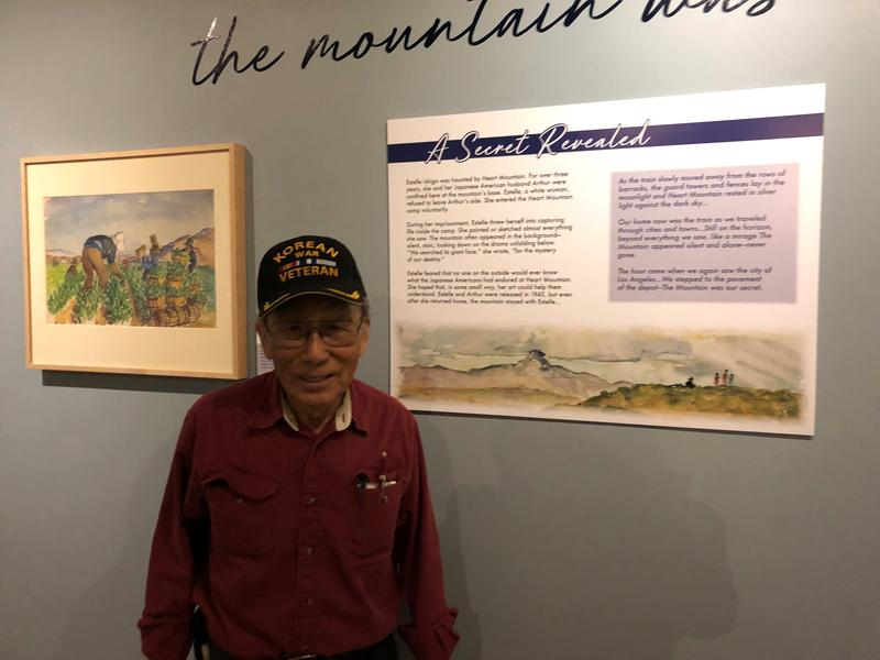 Bacon Sakatani stands in front of one of Estelle Ishigo's watercolors in the new exhibit at Heart Mountain.