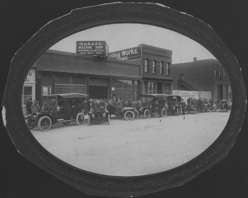 Storefront of Lovejoy Novelty Works with cars in front, 1908. Box 1, Elmer Lovejoy papers.