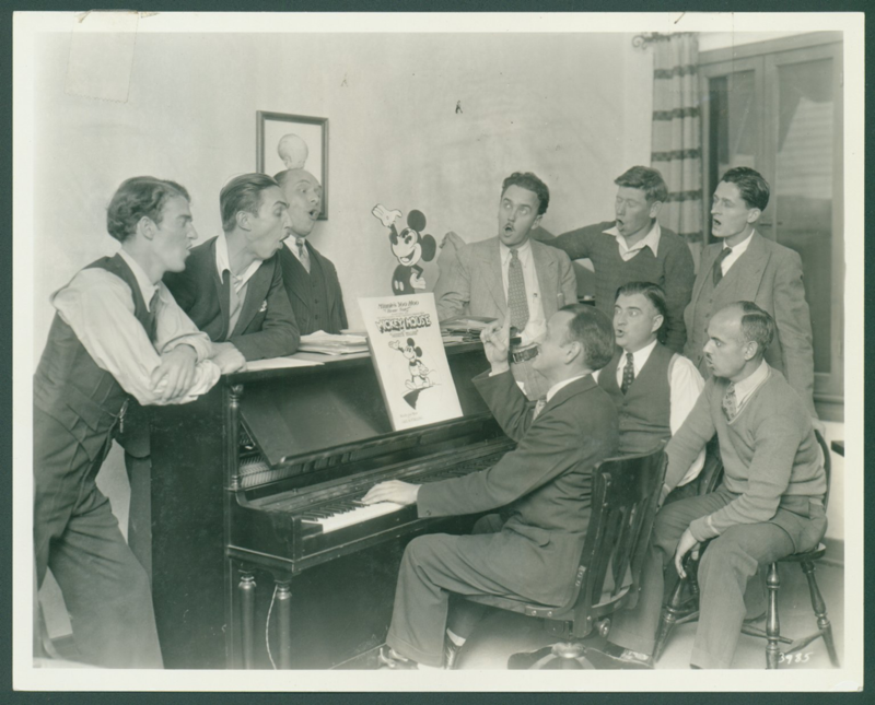 "Photo of Carl Stalling playing the piano while Disney animators sing along to ""Minnie's Yoo Hoo."" Standing behind the piano, Walt Disney is second from the left and Ub Iwerks is third from the right, undated. Carl Stalling photo files."
