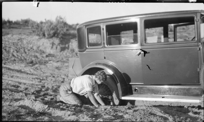 "Ester Robinson digs the car out of mud near Acoma, New Mexico during the ""Gasoline Gypsies"" road trip, 1928. Box 105, Grace Robinson papers."