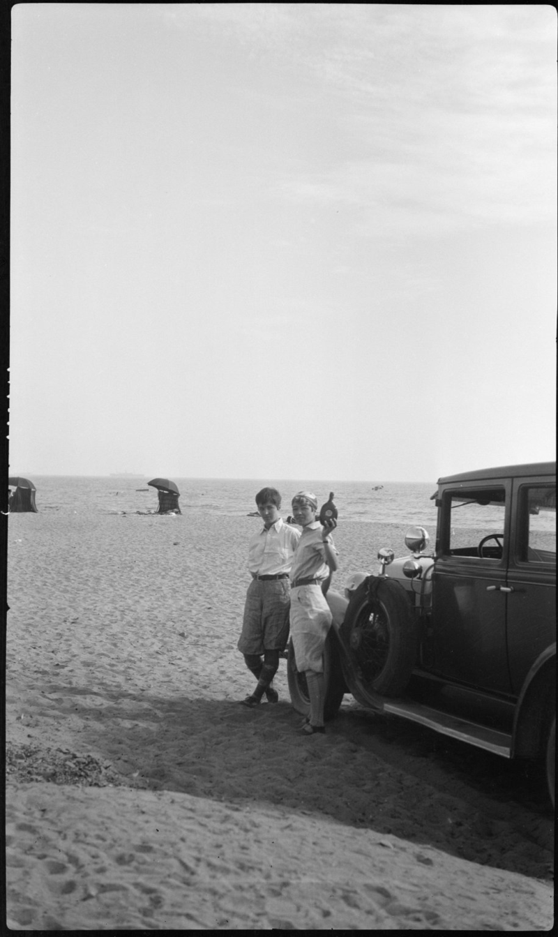 Grace and Ester Robinson standing with their car on the beach in Santa Monica, California, holding a bottle of water from the Atlantic Ocean. Box 105, Grace Robinson papers.