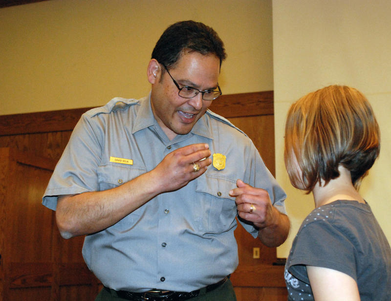 "Supt. Vela describes the significance of the NPS badge to a 4th grade student from Donald Stalker Elementary before awarding a Jr. Ranger badge to her at the completion of an ""Every Kid in a Park"" visit, sponsored by Grand Teton Lodge Co. (May, 2015)"