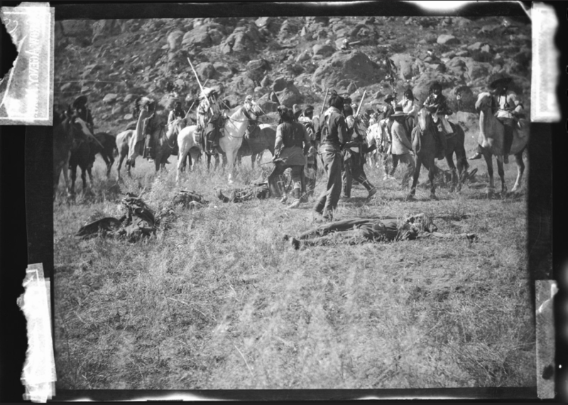 Photograph taken by Richard Throssel of a large group of men on horses, on foot, and on the ground, reenacting a battle, circa 1902-1920s. Box 12, Richard Throssel papers.