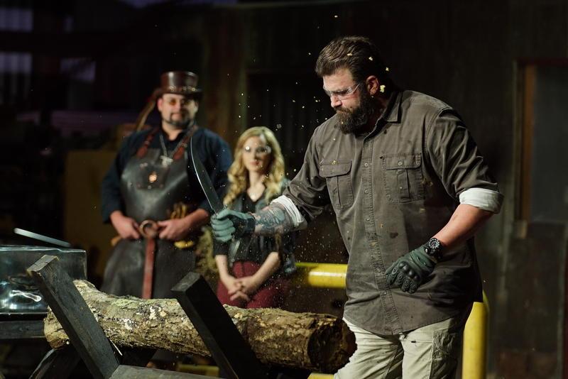 Zeke Stout testing a weapon. Ashley Hlebinsky and Trenton  Tye observe.