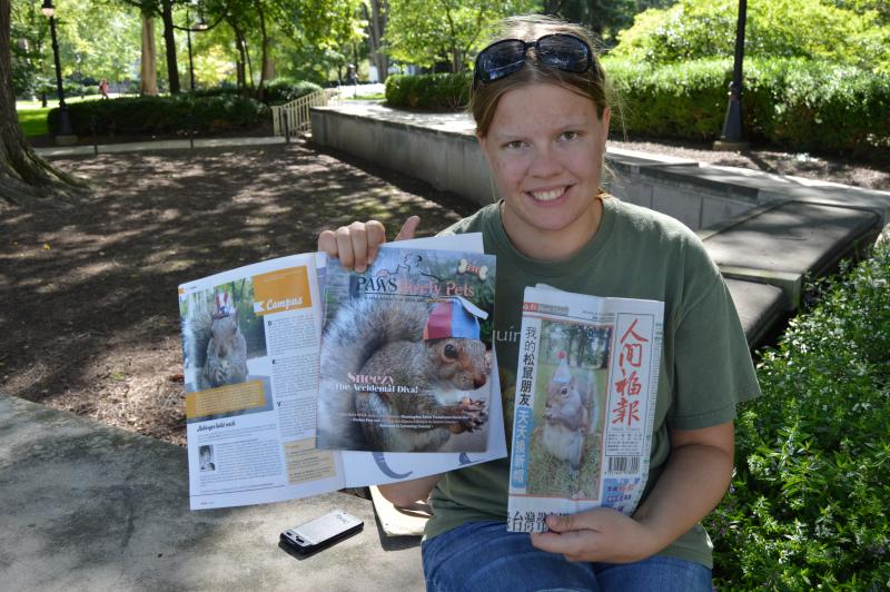 Mary Krupa showing off news articles about Sneezy the Squirrel