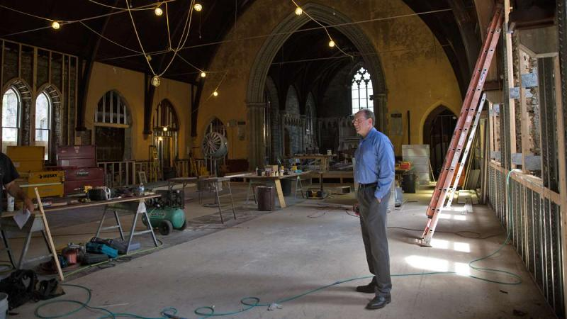 Man standing in church being renovated.