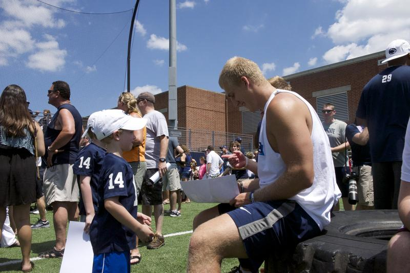 Football player signs autograph