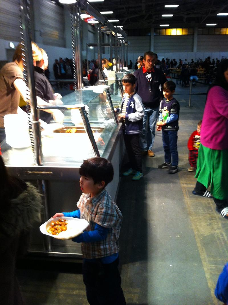 Refugees at cafeteria style dinner line.