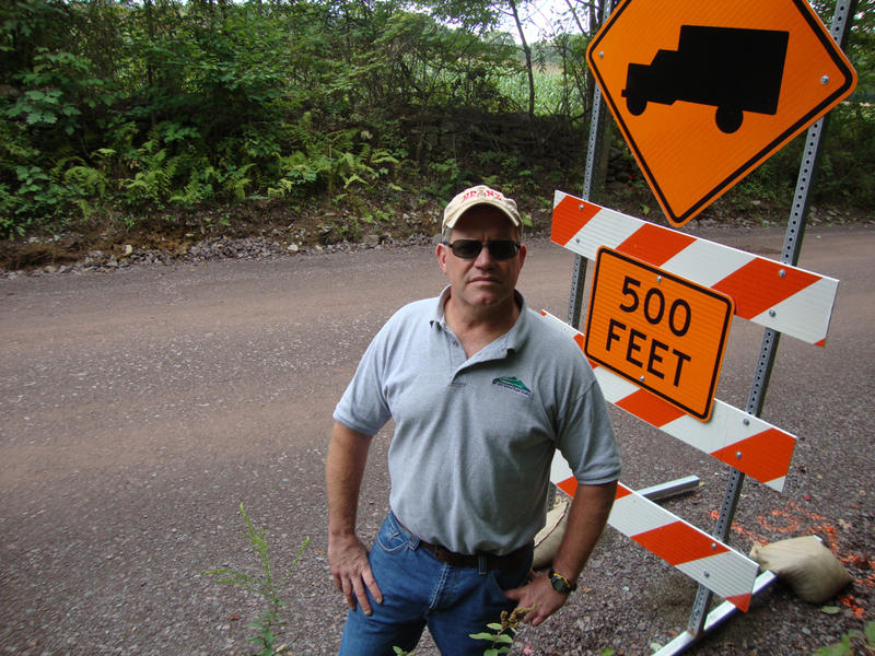 Tim Ziegler next to construction sign on dirt road.