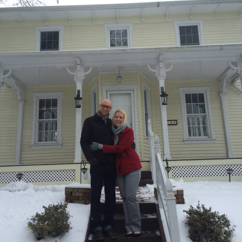 A couple in front of a yellow house.