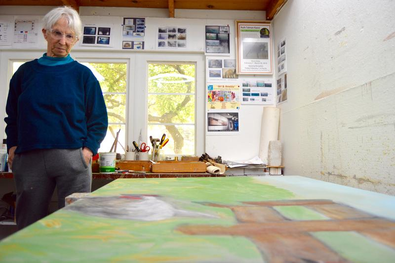Older woman looks down at painting in a studio