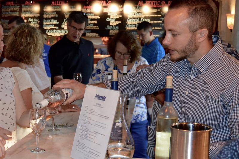 Man pours glass of wine at a bar