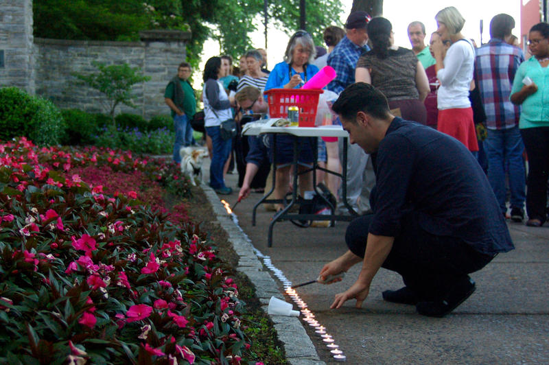 Student lights candles.