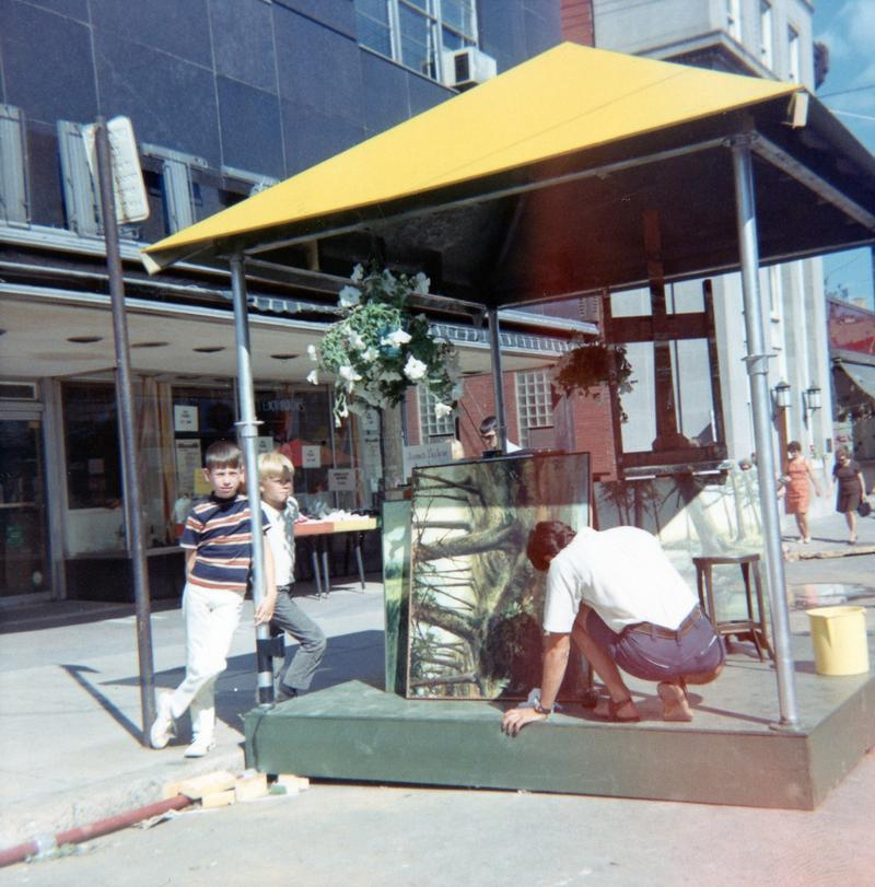 An artist sets up in a booth on College Avenue, 1967.