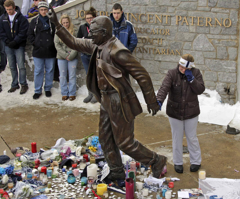 In this Jan. 22, 2012 file photo, a woman pays her respects at a statue of former Penn State football coach Joe Paterno outside Beaver Stadium on the Penn State University campus after learning of his death in State College, Pa. Paterno was 85.