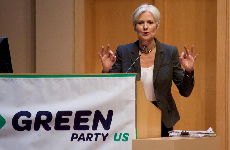 "Jill Stein in front of a ""Green Party"" banner."