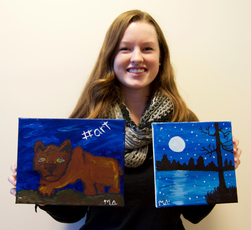 Meghan Shiels holding a painting of a Nittany Lion and a night scene.