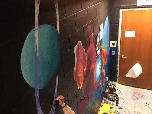 A student painting a mural outside the planetarium.