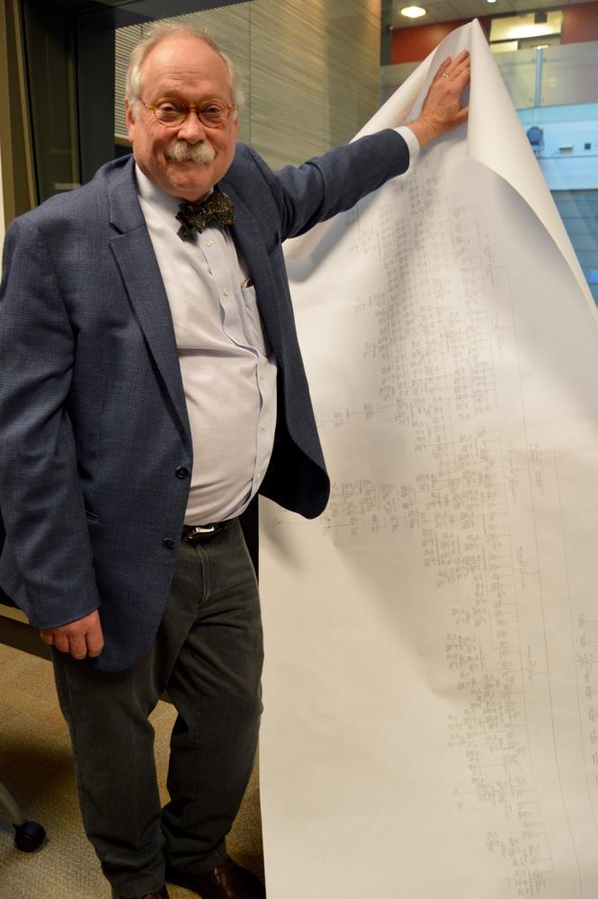Dr. Holmes Morton holding up a huge sheet of paper.