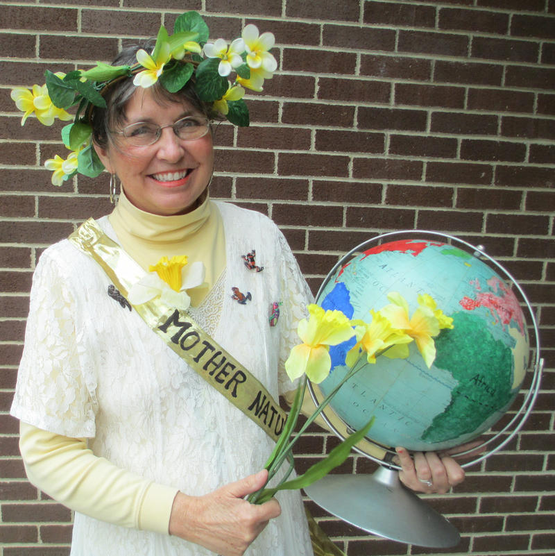 Sue Shaffner in a white dress holding a globe and daffodils.