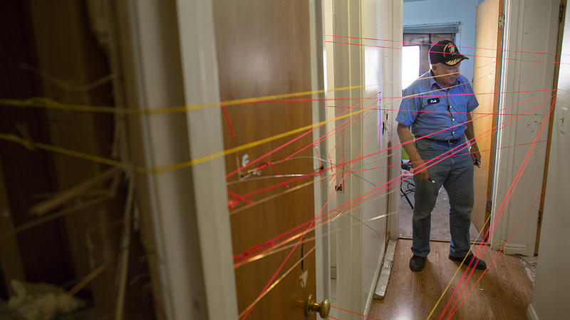 """Dub"" Lawrence at one of the SWAT crime scenes with strings marking bullet paths."
