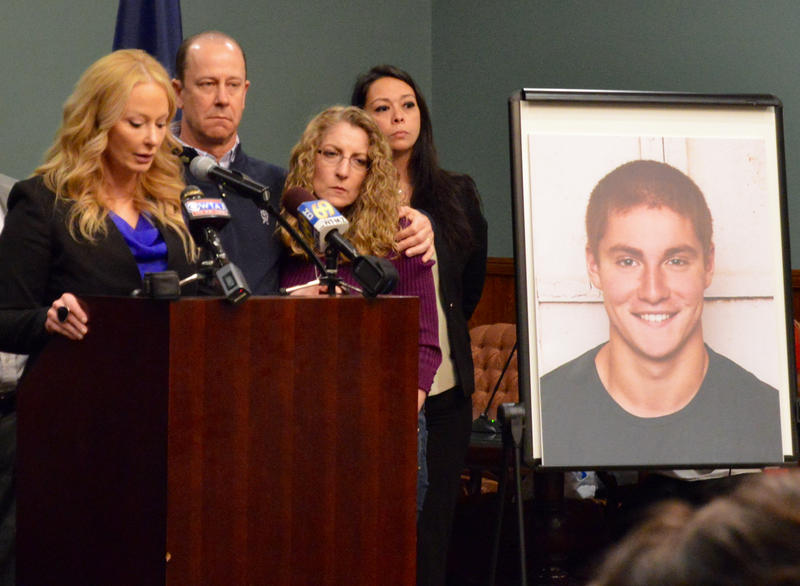Centre County District Attorney Stacy Parks Miller at podium next to a photo of Timothy Piazza and with his parents in person