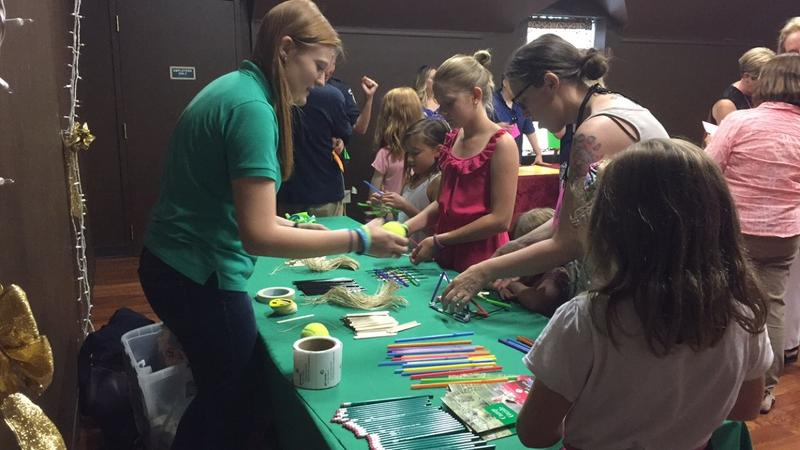 Local girls create structures from popsicle sticks and straws to hold up a tennis ball at the Girl Scouts of the USA table at the Hidden Figures showing event.