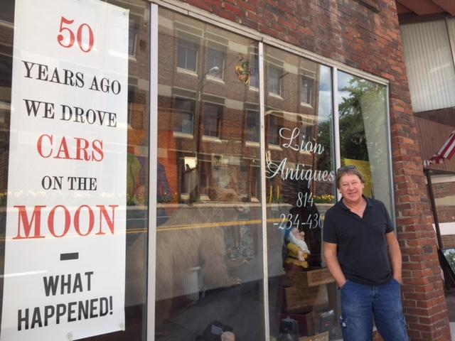 Lion Antiques Storeowner David Godiska stands by the sign he hopes will inspire Penn State students to think about space exploration.