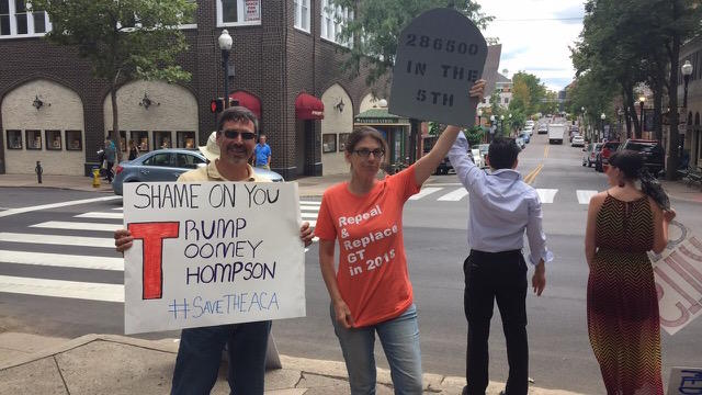 Penn State professor Jonathan Brockopp and Webster's Bookstore Cafe owner Elaine Meder-Wilgus hold up signs by the Allen Street Gates.