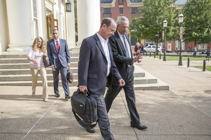 Jim Piazza (front left) and Thomas Kline spoke as they left the courthouse in Bellefonte on August 30, 2017.