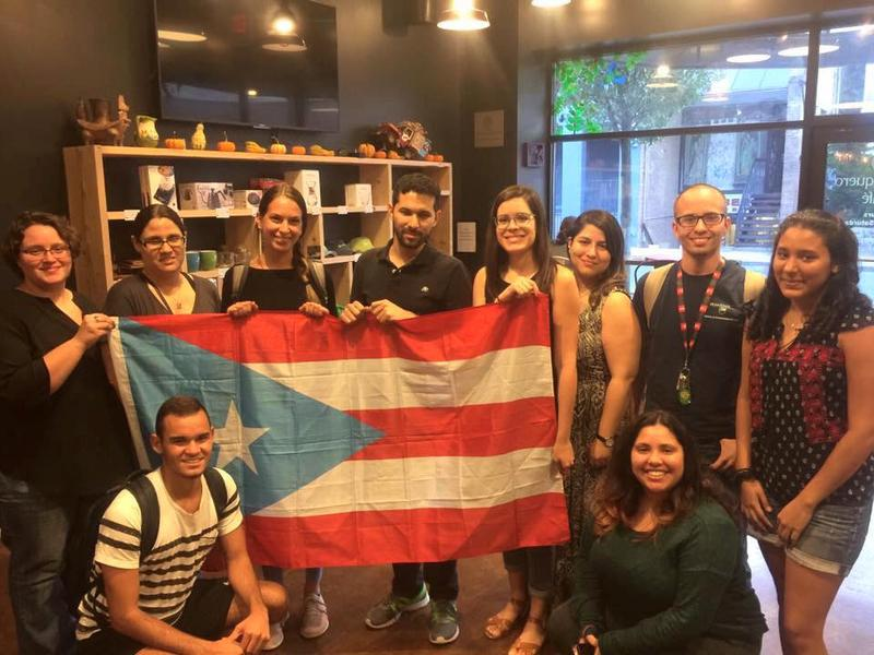 Members of the Penn State Puerto Rican Student Association stand with the Puerto Rican flag.