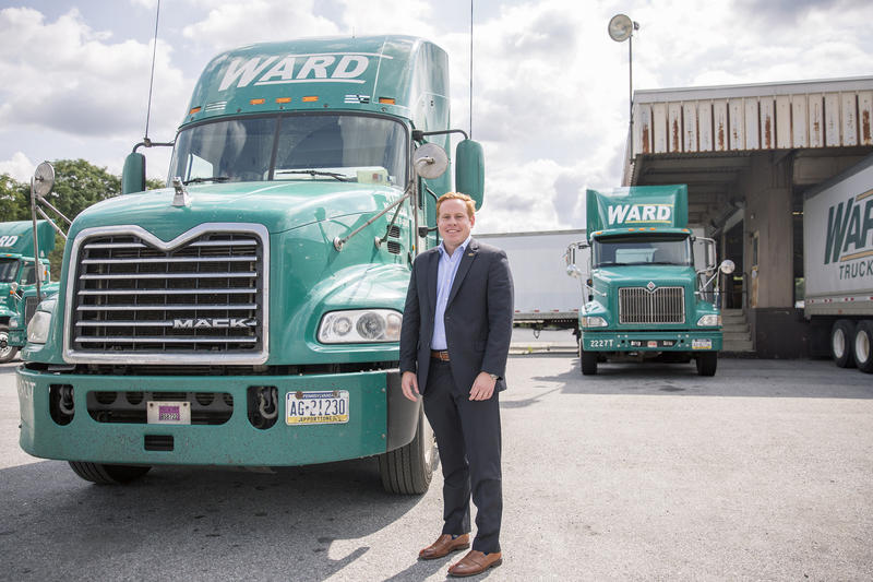 Bill Ward poses for a photo with one of new trucks