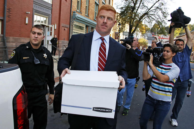 Mike McQueary leaves the Centre County Courthouse Annex in Bellefonte, Pa., Monday, Oct. 17, 2016 surrounded by reporters.