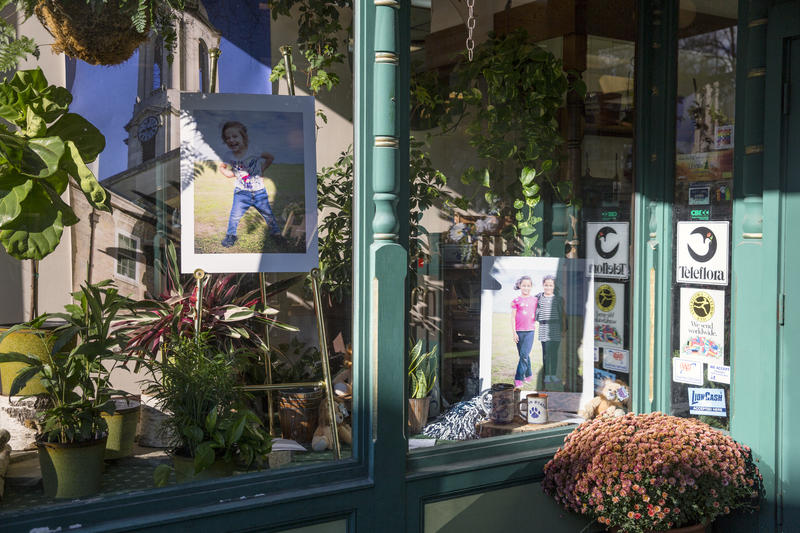 Portraits of refugee children are on display in the window of Woodrings Floral in downtown State College.
