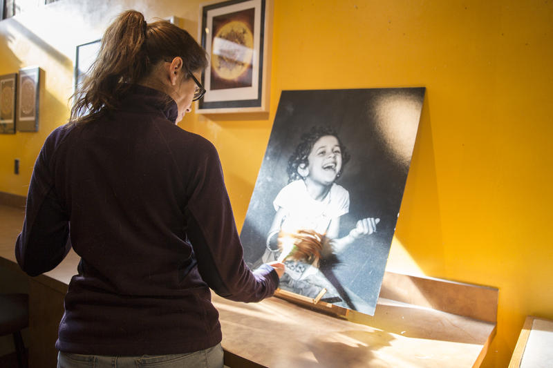 A woman pauses to look at a portrait of Ruqaya, a refugee child, in Webster's Bookstore.
