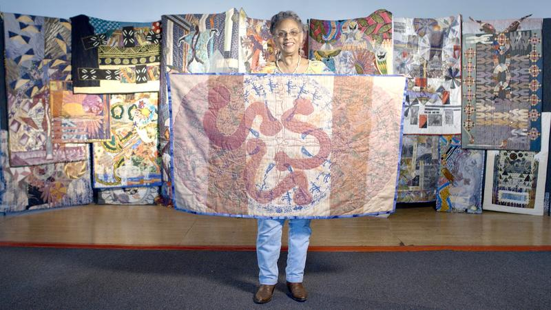 Tina Williams Brewer with a collection of her story quilts.