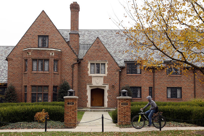 A bicyclist rides past Pennsylvania State University's shuttered Beta Theta Pi fraternity house Thursday, Nov. 9, 2017, in State College, Pa.