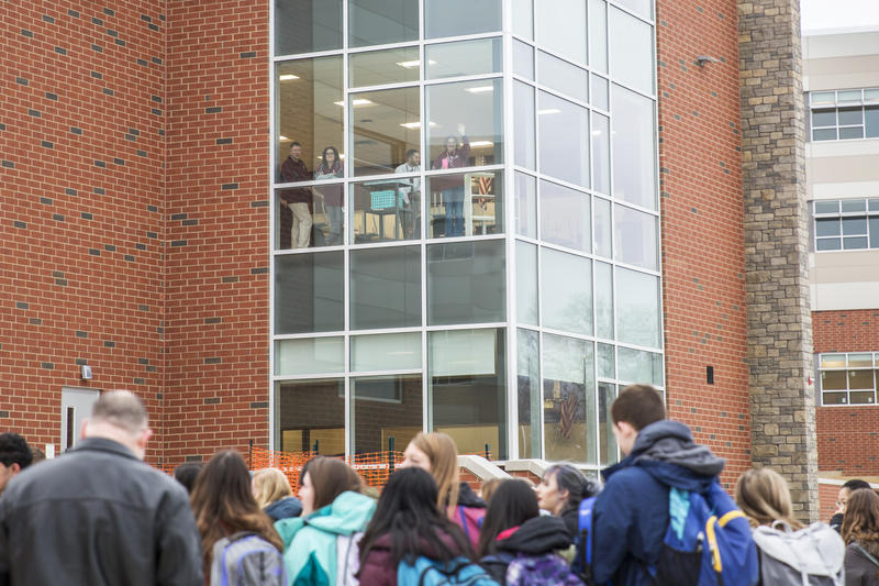Faculty and staff wave at students and welcome them to the new south buildings on first day of classes.