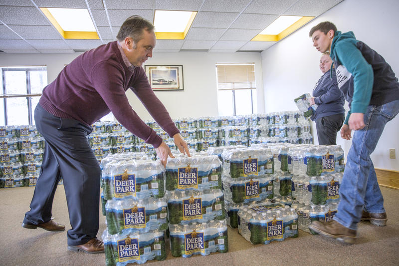State Sen. Jake Corman helped move cases of bottled water to distribute to residents. Corman and Rep. Mike Hanna said they would help the area find funding.
