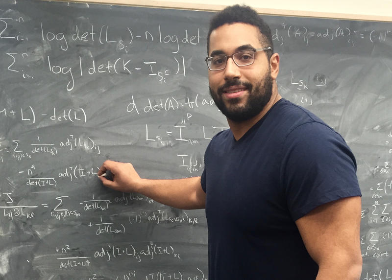 John Urschel does math problems on a blackboard.