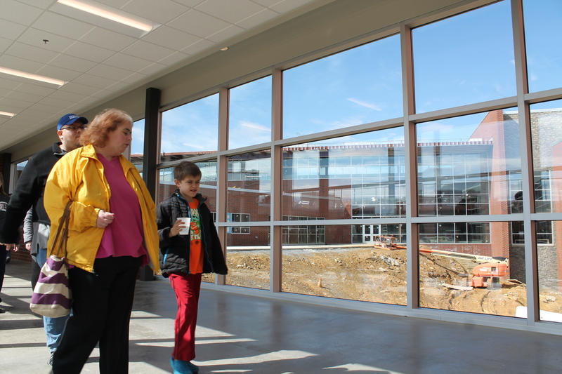 Community members cross a glassed-in hallway from the cafeteria to the classroom area. Outside is a future courtyard and the partially constructed library.