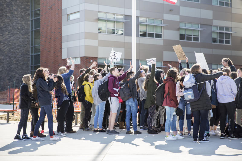 Students who walked out of class to protest waved at their fellow students from the school courtyard.
