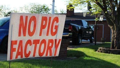 In this May 21, 2018 photo, a sign opposing an industrial hog farm is displayed at a home in Berwick, Pa. Residents who complain about foul smells from the nearby hog farm have taken their fight to the Pennsylvania Supreme Court.
