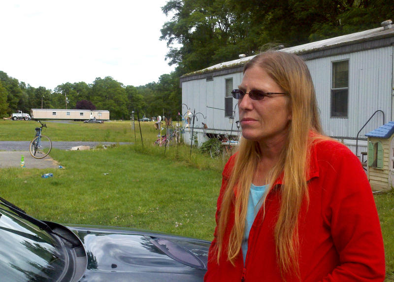 Deb Eck stands in front of her trailer at Riverdale Mobile Home Park on the outskirts of Jersey Shore. Across the park, other residents who can afford it have their mobile homes moved elsewhere.
