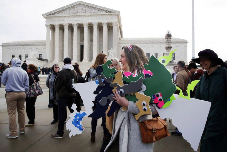 Ashley Oleson, with the League of Women Voters of Maryland, carries signs of the state's districts, before oral arguments in Benisek v. Lamon in front of the Supreme Court, Wednesday, March 28, 2018.