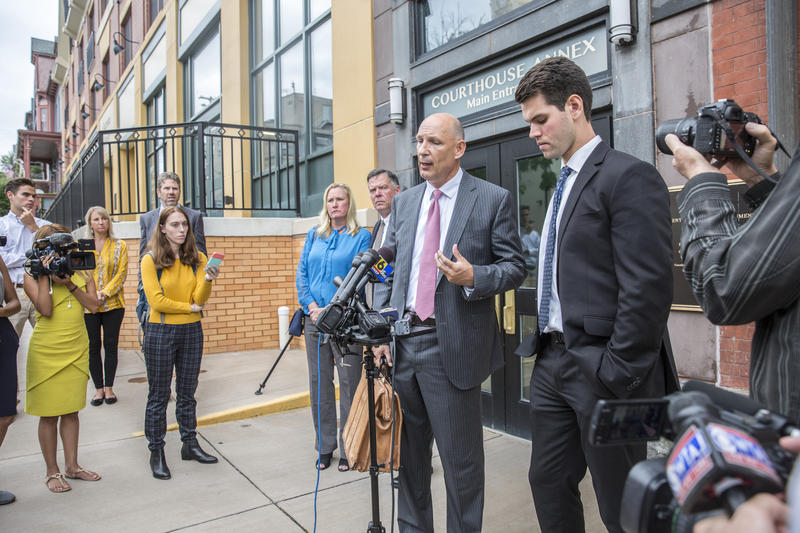 Philip Masorti (second from right) spoke to reporters outside the courthouse after the sentencing of his client, Ryan Burke (right), on Tuesday.