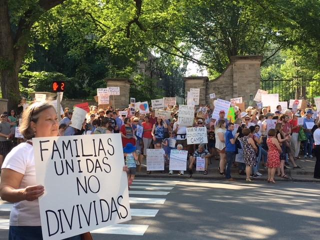 """Protesters hold signs at the """"Families Belong Together"""" rally in State College."""