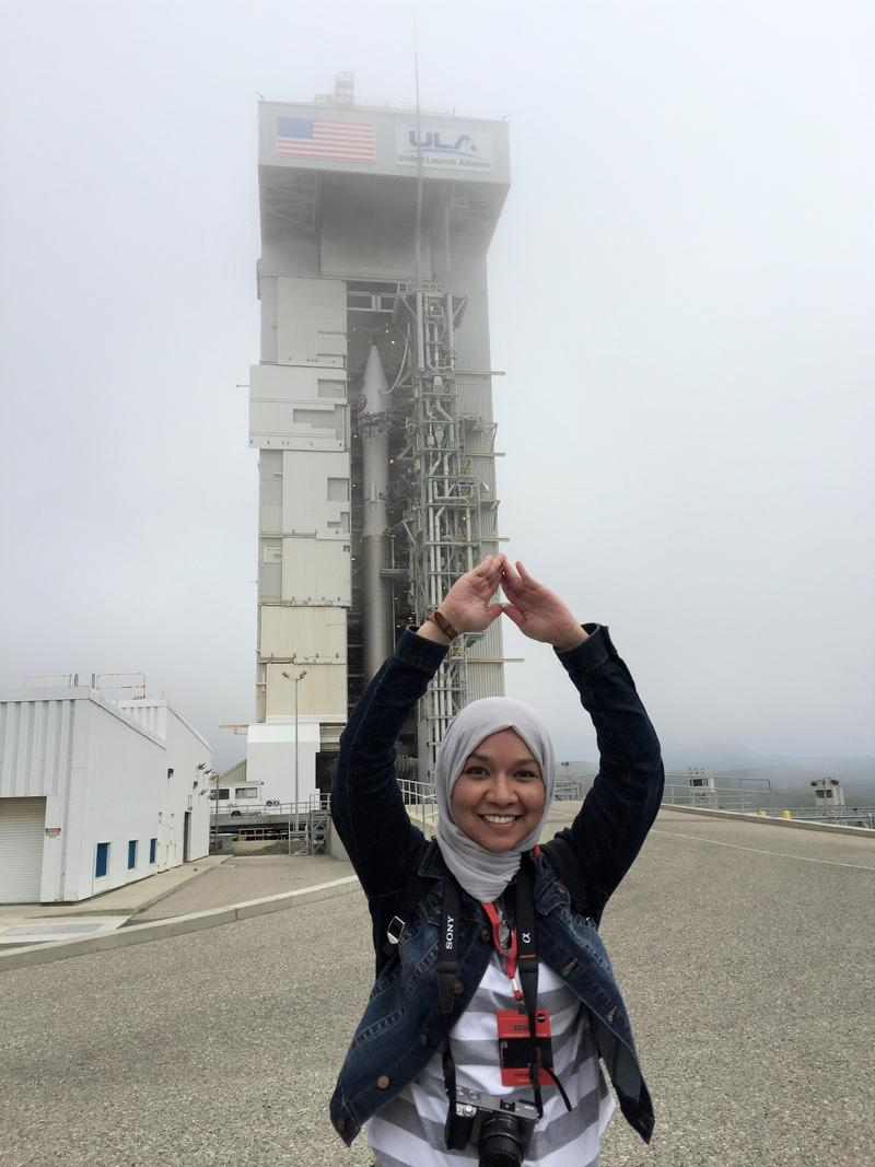 Essayist Sarah Khalida in front of the Atlas V rocket.