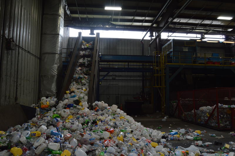 Recyclable plastic being fed onto a conveyor belt for workers to sort