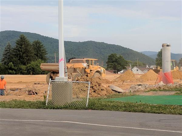 A construction vehicle moves earth for the construction of the new Rogers Stadium for Bellefonte Area High School.